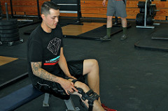 man putting on knee brace after injury