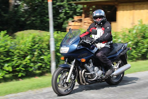 Person in black riding motorcycle wearing a black helmet and jacket