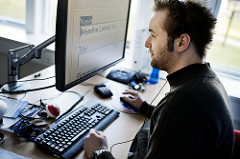 Man with beard looking at elevated computer screen