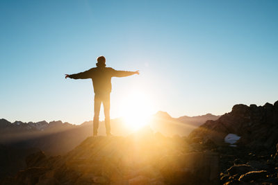 Man standing on mountain looking out at the sun