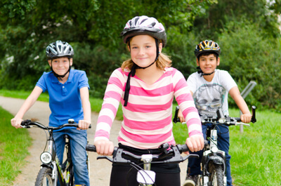 A girl and two boys on bicycles