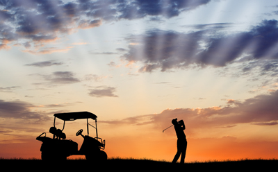 Golfer swinging club into the sunset