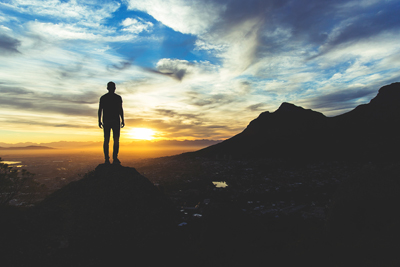 Guy standing at the top of the mountain in the sunset