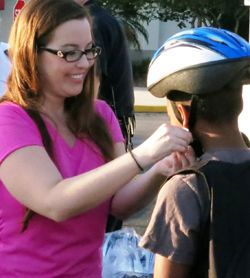 Kati Fitting a Helmet on a Kid