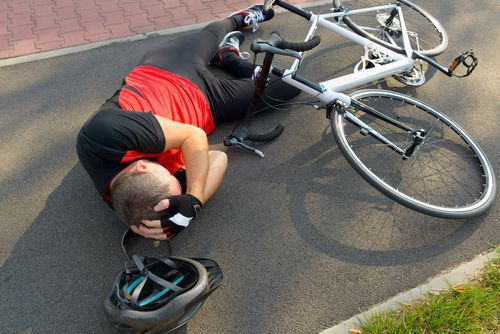 Cyclist on the Ground Holding His Head