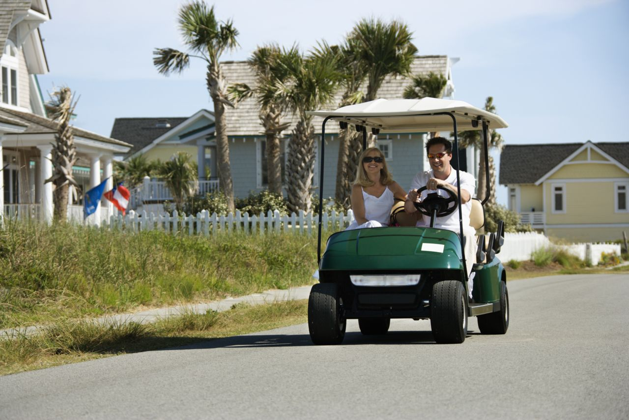 A Couple Driving a Low Speed Vehicle in a Neighborhood