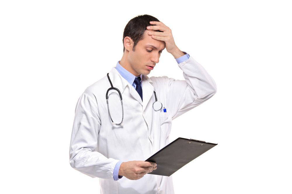 Worried Doctor With Hand On His Head And Patient Chart In His Hand