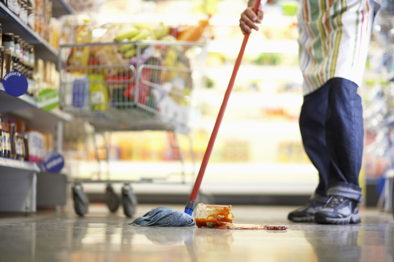 Employee Cleaning the Floor of a Grocery Store