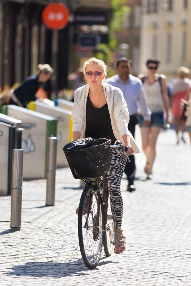 Lady Riding Her Bicycle on a Sidewalk
