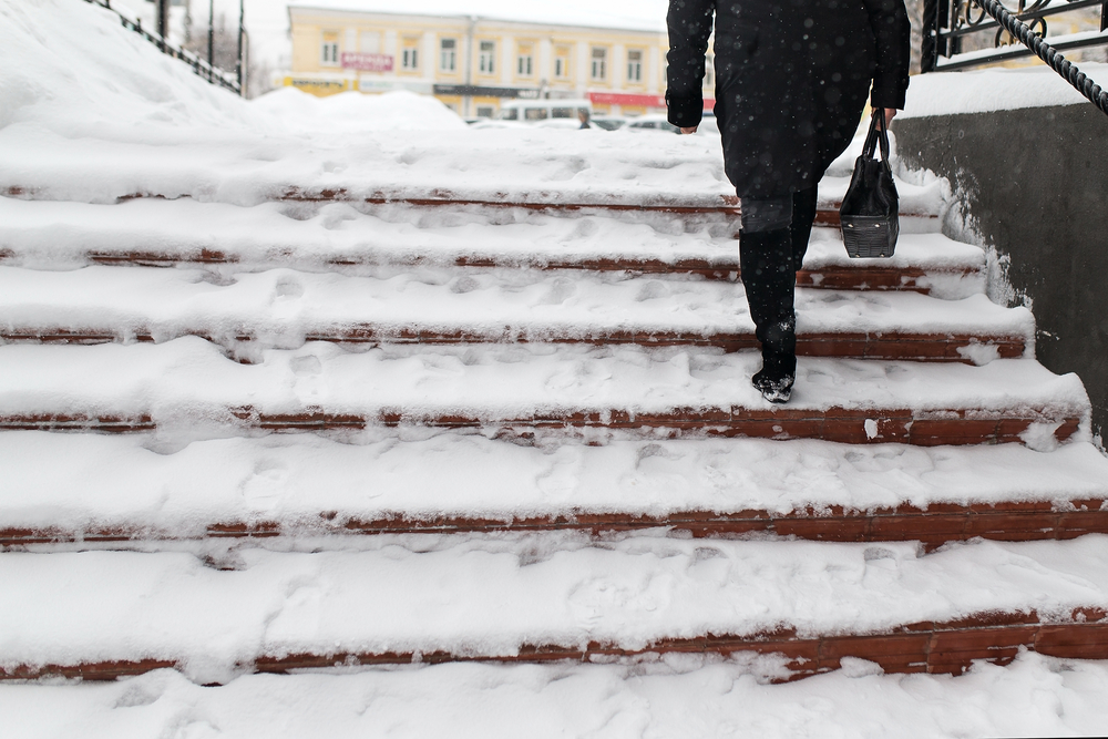 Woman climbing snowy steps to public building