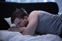 A Man Laying in Bed Having a Hard Time Sleeping