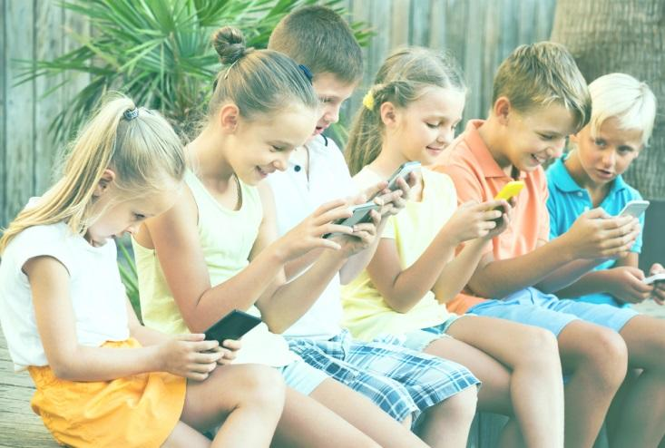 Row of children staring at phones