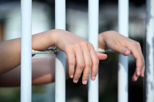 Hands between prison bars