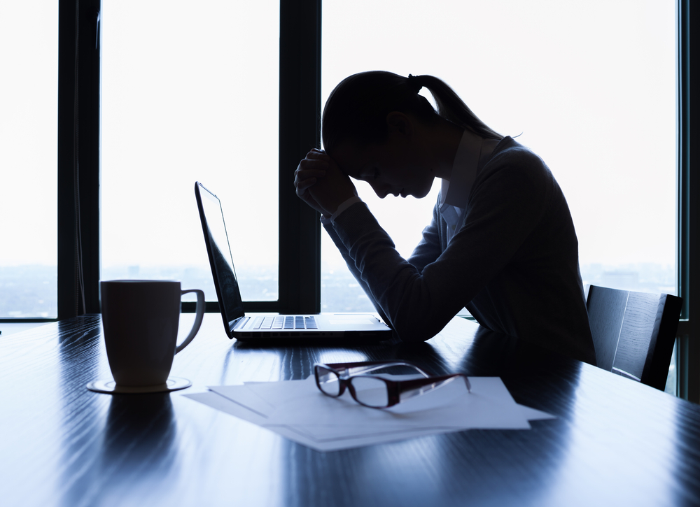 Woman in office with head bowed in sadness