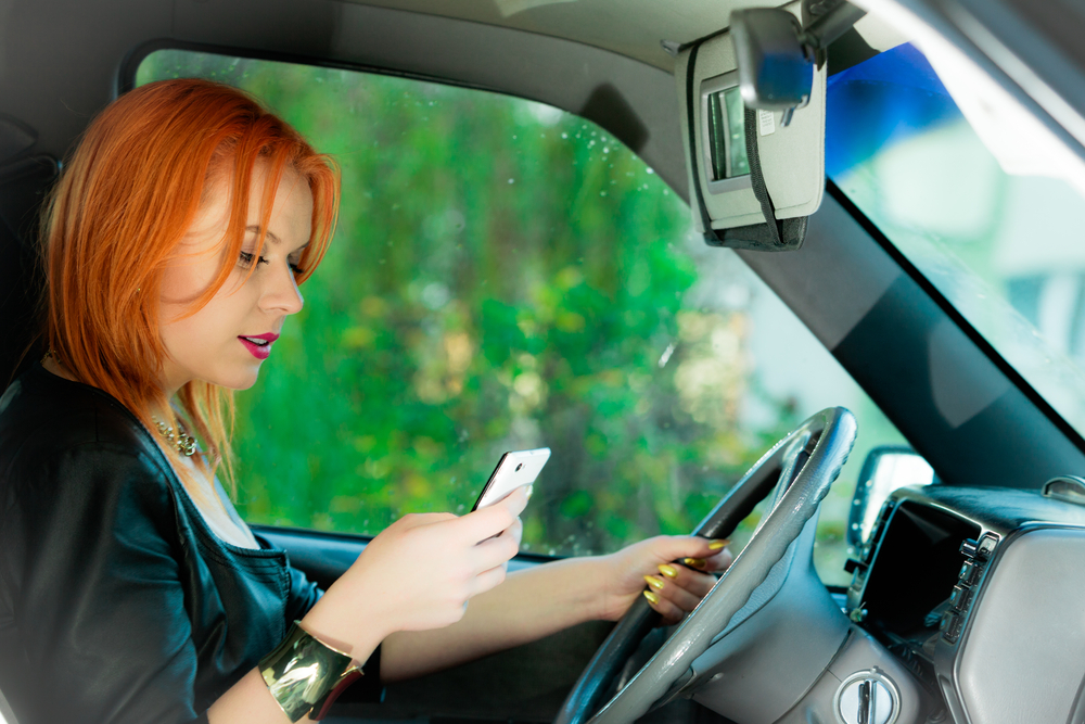 Girl typing while driving