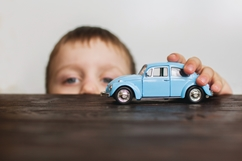 Child Playing With a Toy Car Showing a Child Car Accident Concept