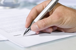 Hand Holding a Pen Signing a Medical Release Form