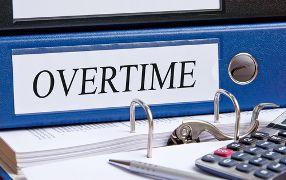 Blue Overtime Folder Sitting Next to a Calculator