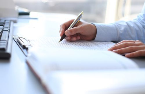A Businessman Holding a Pen Over a Legal Document