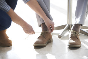 Caregiver tying elderly man's shoes