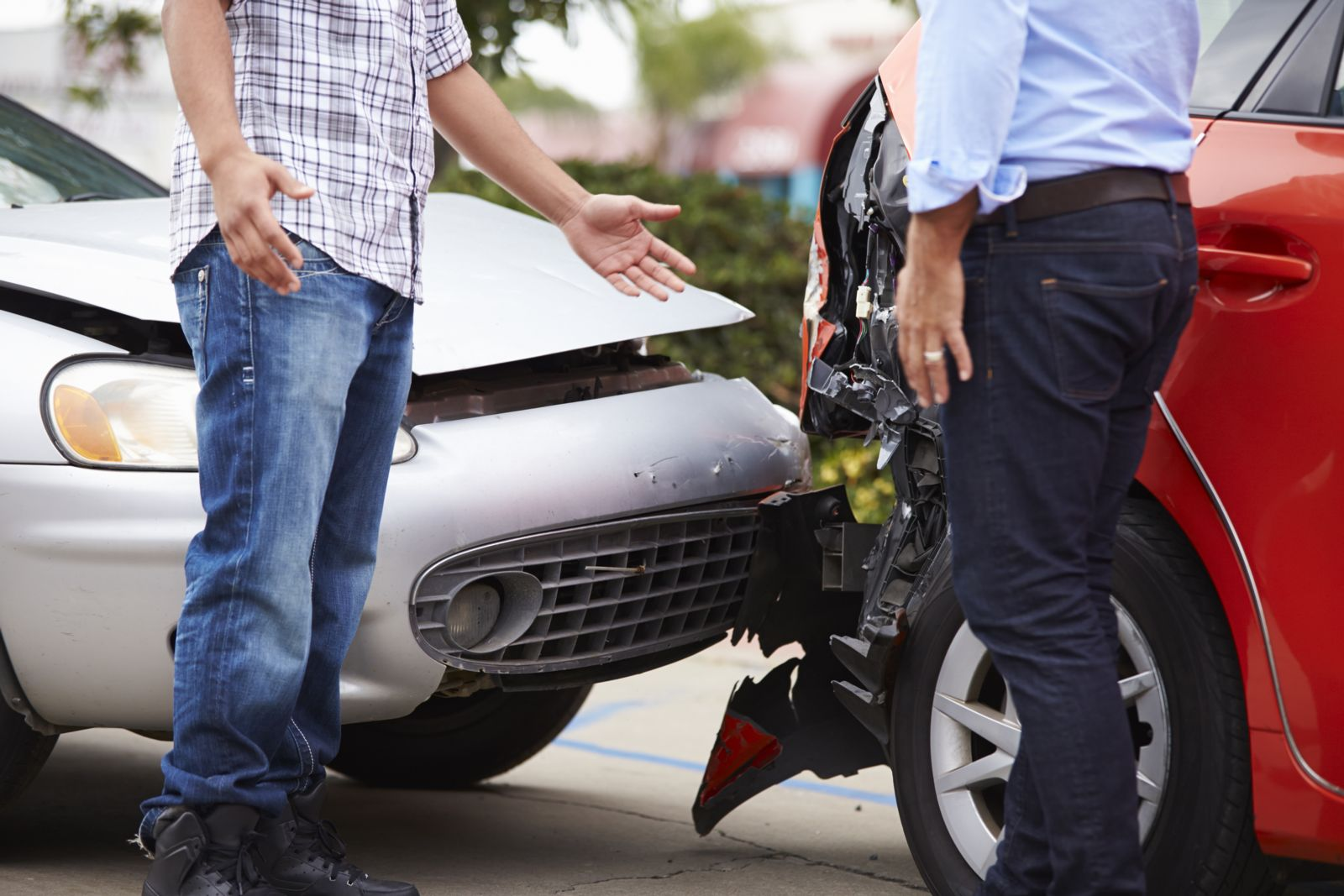 Two men exchanging insurance information after car accident.