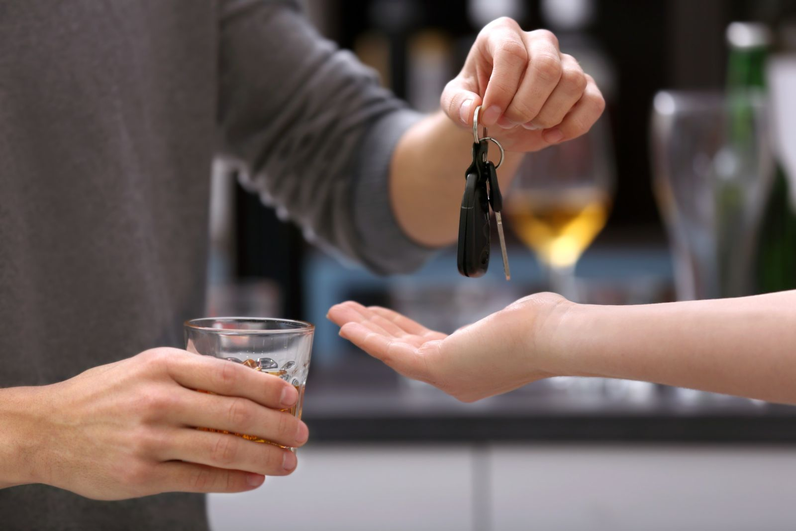 Intoxicated Man Holding a Drink and Handing Over His Keys