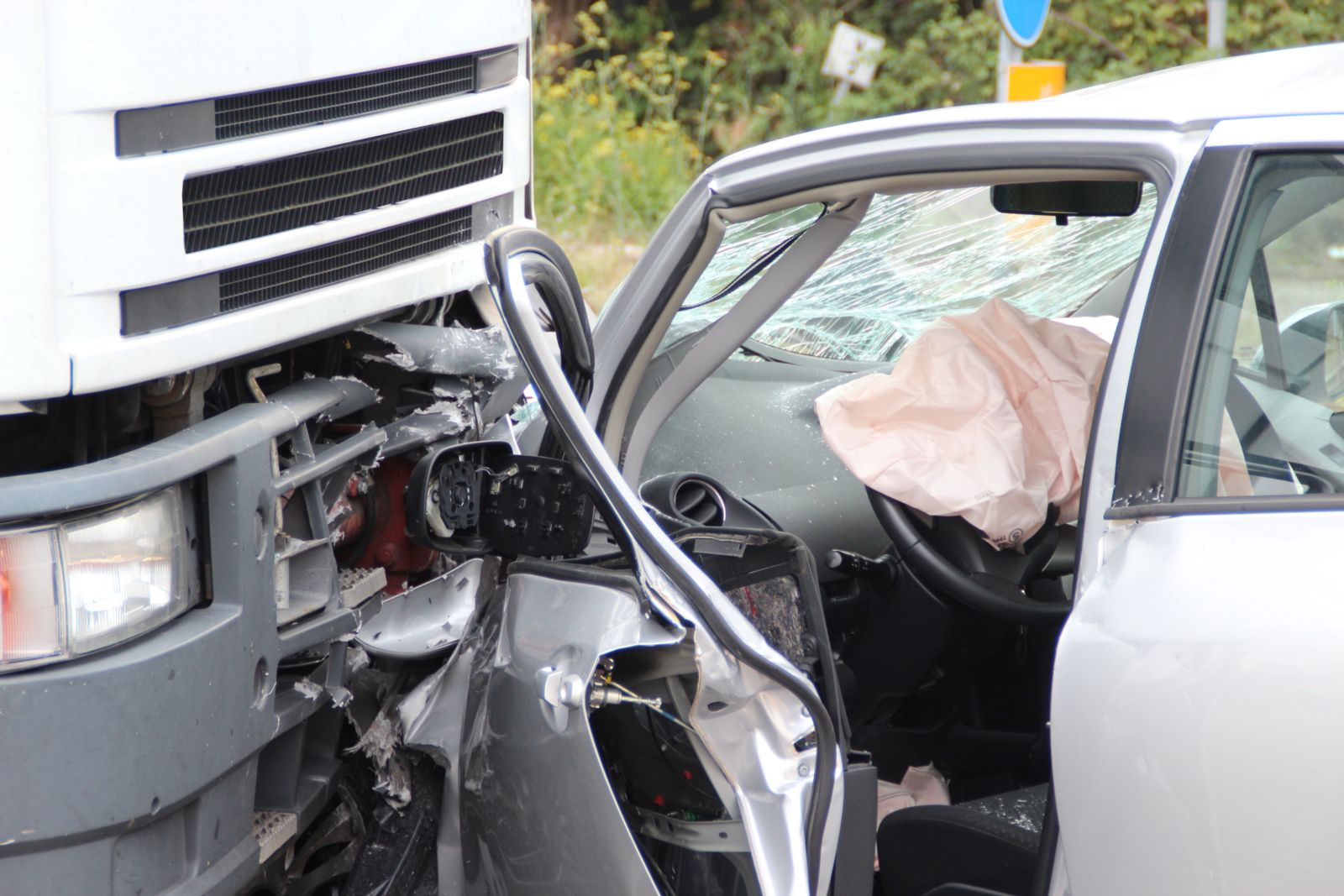 Semi truck hits passenger car head on causing severe damage and injuries.
