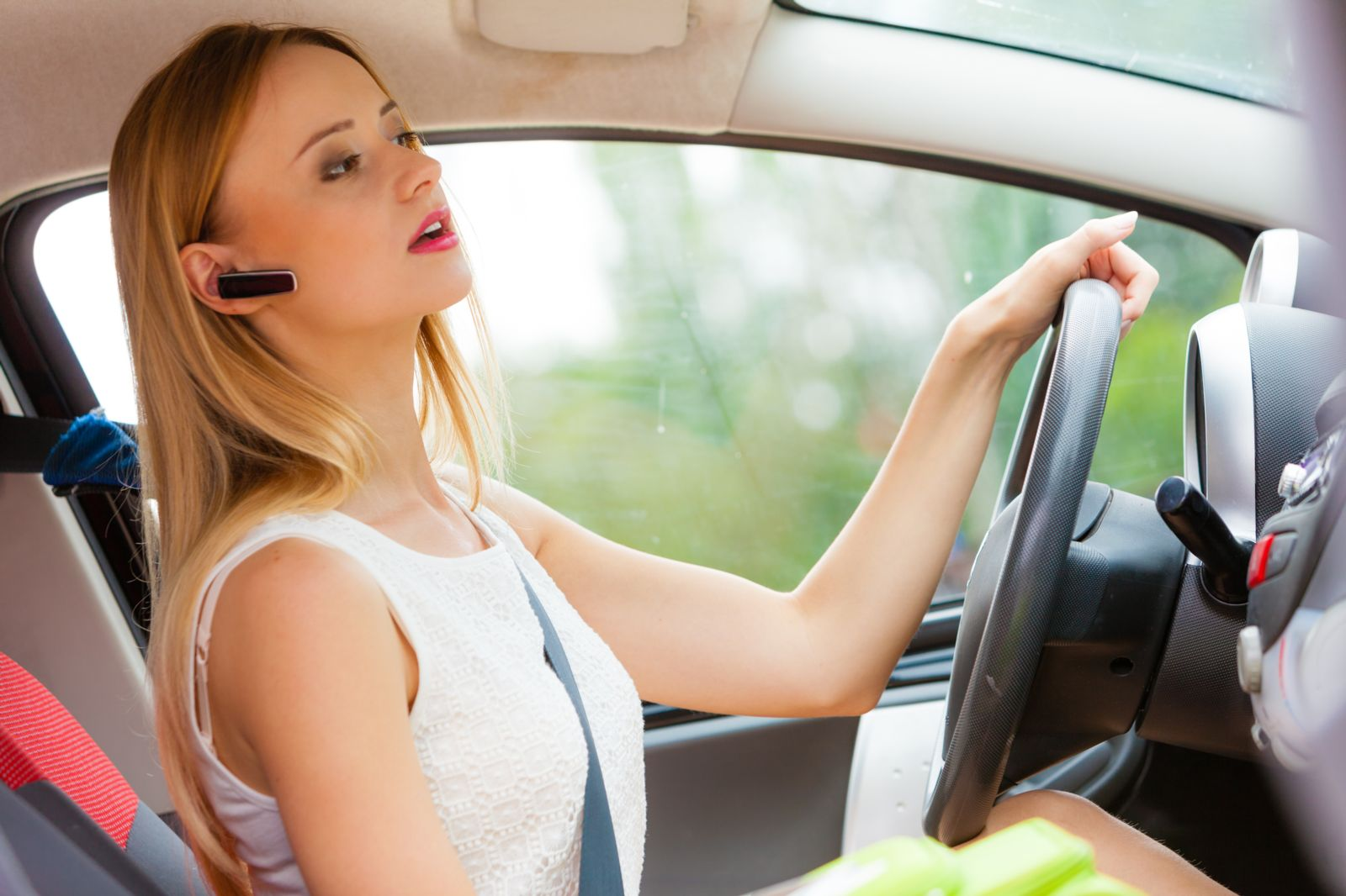 Woman driving while speaking into a hands-free device.