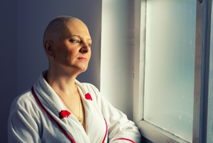 bald woman looking out window