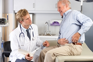Doctor examining man with hip pain