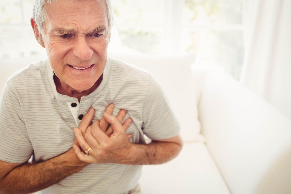 older man clutching chest having heart attack