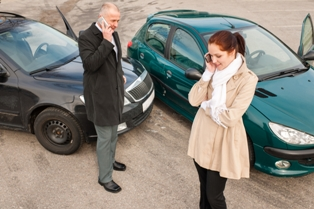 Man and woman talking on cell phones after car accident