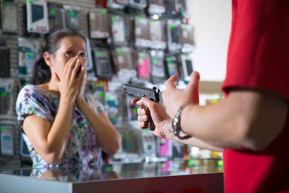 Store clerk being robbed at gunpoint