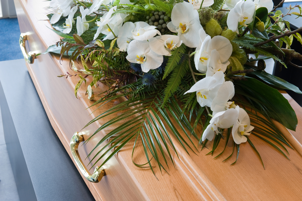 coffin with white flowers on top