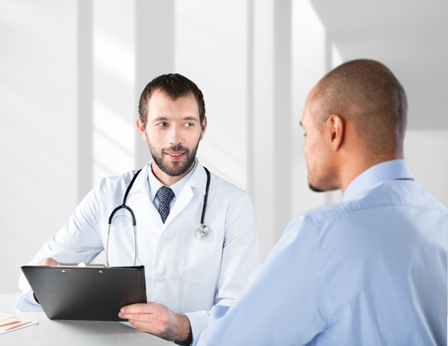 Doctor with clipboard talking to patient