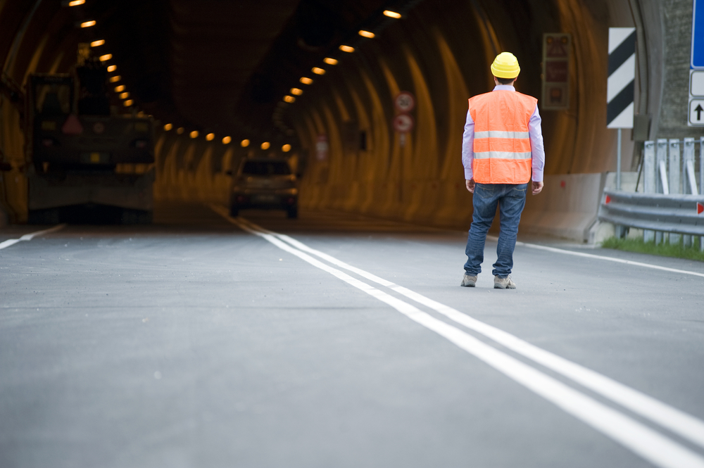 Worker standing in front of highway tunnel