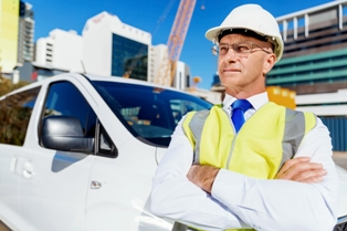 Supervisor standing in front of a car at a construction site