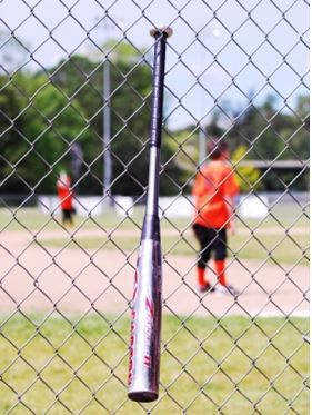 Baseball bat hanging off of a fence