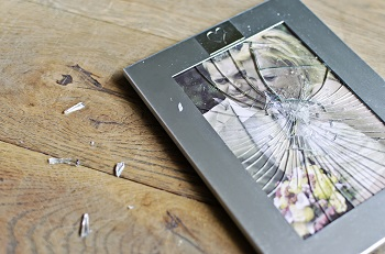 Broken wedding picture frame of couple facing adultery and divorce