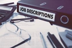 Job Description binder and other paperwork on a desk