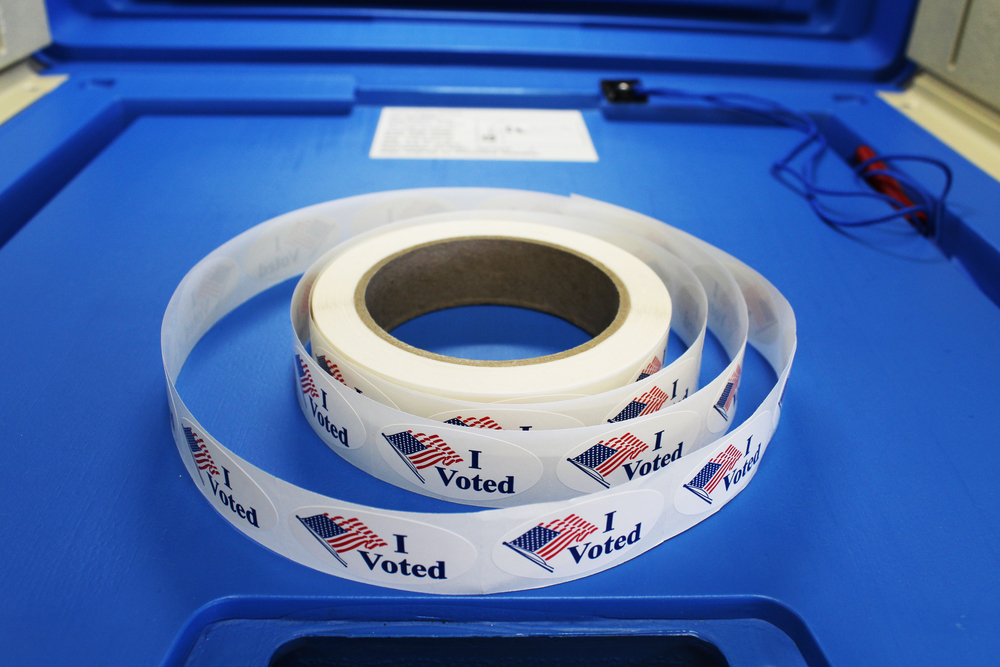 Spool of I Voted stickers on a blue table