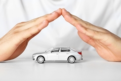 Hands Held Over a Car Mimicing Car Insurance Policy Protections