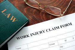 Work Injury Claim Form With a Green Law Book and a Pair of Glasses