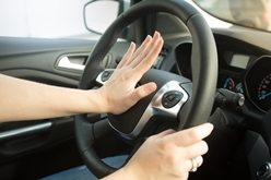Woman With Hand on Horn While Driving
