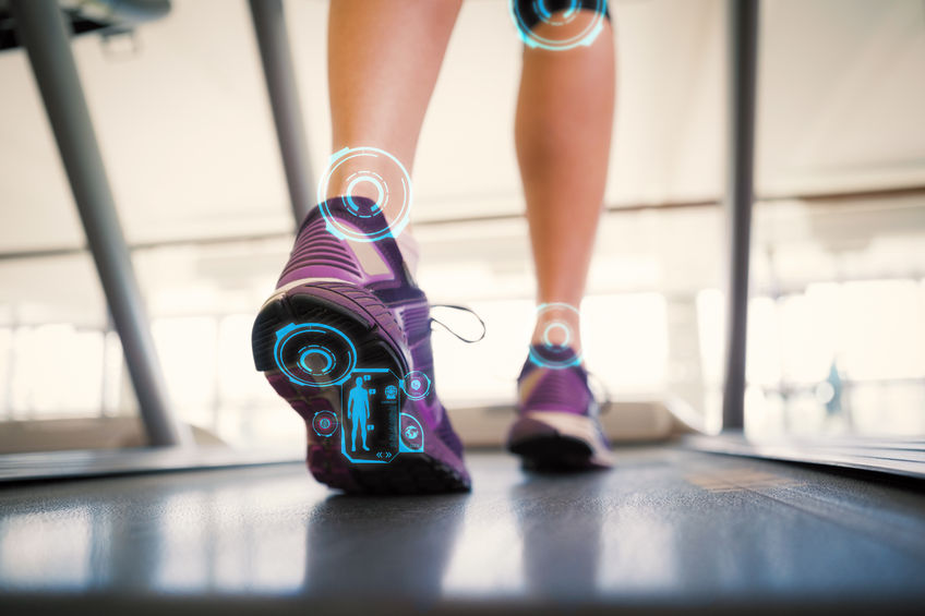 Woman walking on the treadmill against fitness interface