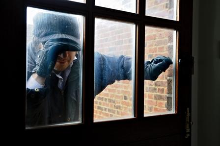 Burglar at window looking in house