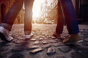 Two people walking with pronation on a cobblestone street