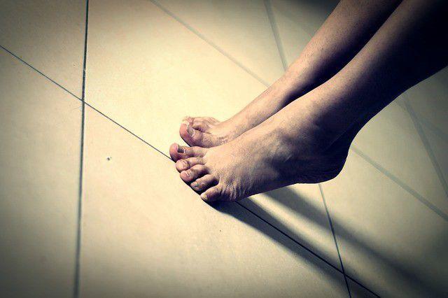 Feet raised on tile floor