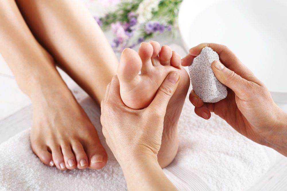 Using a pumice stone on calluses.