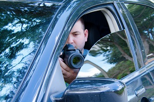 Private investigator takes photos from a car